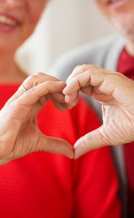 A couple making a heart shape with their hands to showcase heart health at The Gatesworth