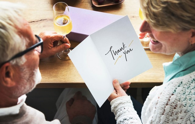 "Senior couple enjoying wine - woman has greeting card with sentiment ""Thank You"""