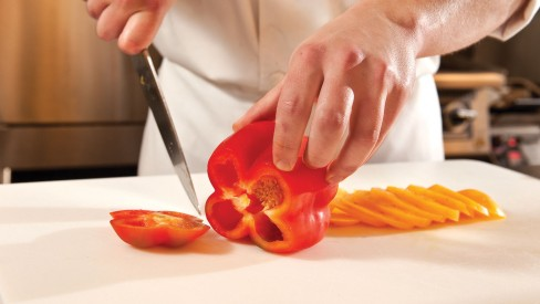 Chef chopping red bell pepper