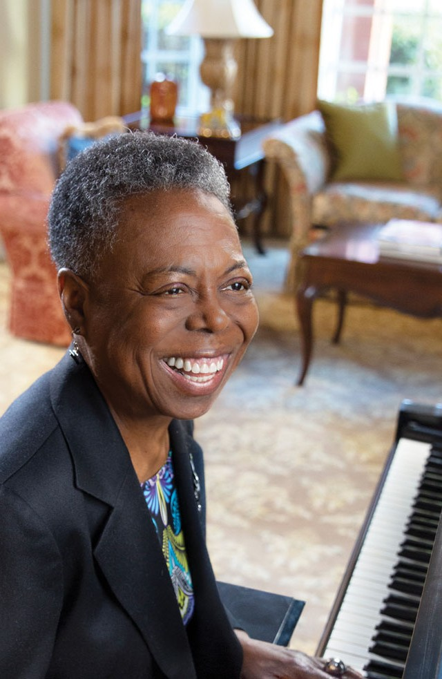 Woman playing the piano and smiling